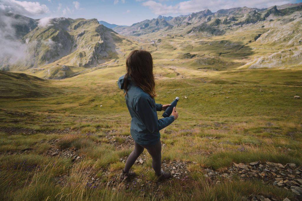 Femme faisant une randonnée en montagne avec sa gourde.