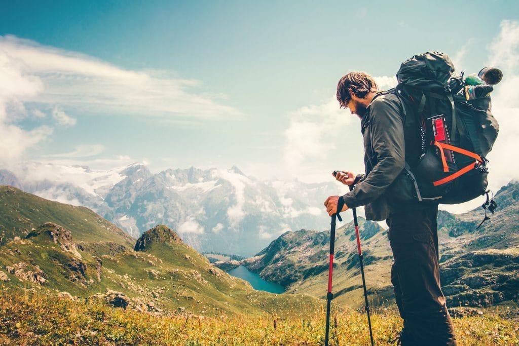 Homme vérifiant son GPS de randonnée lors d'un trek dans les Alpes.